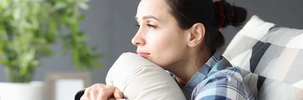 Portret młodej smutnej kobiety siedzącej na kanapie kobiecej koncepcji samotności i depresji