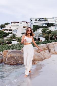 Portret młodej, spokojnej, szczęśliwej, szczupłej kobiety rasy kaukaskiej w topie cami crop i spodniach ustawionych samotnie na skalistej tropikalnej plaży o zachodzie słońca