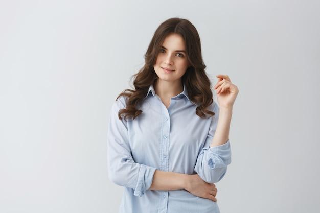 Portret młodej studenckiej dziewczyny z falistymi ciemnymi włosami w niebieskiej koszuli, pewny siebie i delikatny uśmiech.