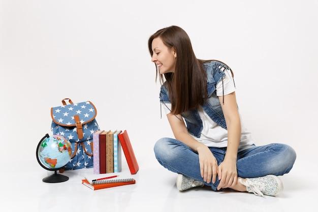 Portret młodej studentki dorywczo zainteresowanej kobiety w dżinsowych ubraniach, siedzącej, patrzącej na kulę ziemską, plecak, podręczniki szkolne na białym tle