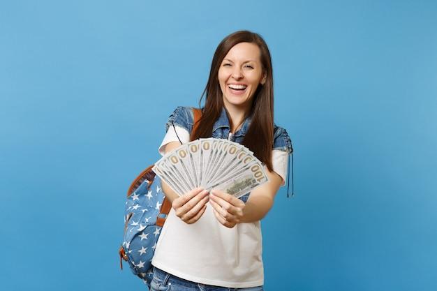 Portret młodej studentki roześmiany wesoły w dżinsowe ubrania z plecakiem trzymającym pakiet wiele dolarów, pieniądze w gotówce na białym tle na niebieskim tle. edukacja w liceum ogólnokształcącym.