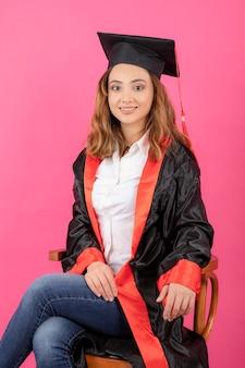 Portret młodej studentki siedzącej na krześle na różowej ścianie.