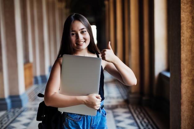Portret młodej studentki z azji korzystającej z laptopa lub tabletu w inteligentnej i szczęśliwej pozie na uniwersytecie lub w college'u,