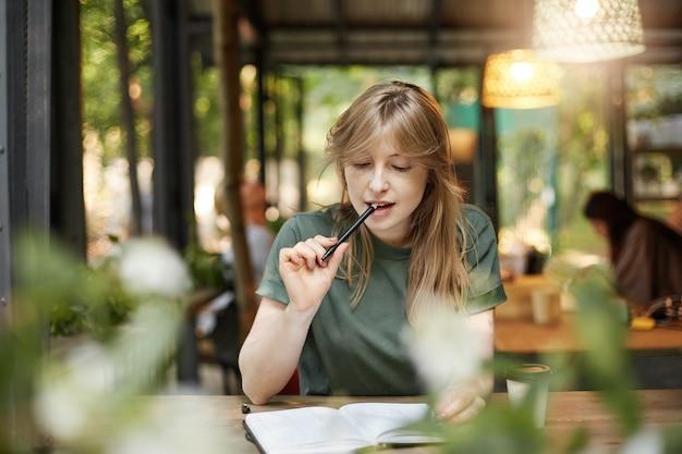 Portret młodej studentki żucia na ołówku w kawiarni, przygotowując się do jej zdania egzaminów