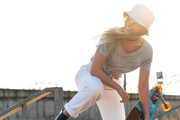 Portret młodej stylowej dziewczyny z longboardem w mieście