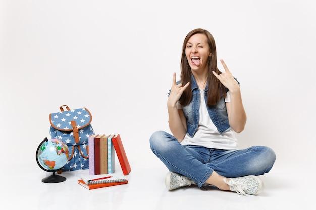 Portret młodej szalonej śmiesznej studentki pokazującej język rock-n-rollowy znak siedzący w pobliżu plecaka na świecie, na białym tle podręczniki szkolne