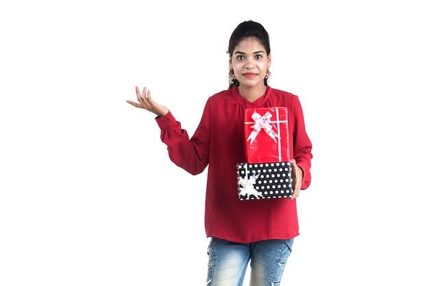 Portret młodej szczęśliwa uśmiechnięta dziewczyna trzyma i pozuje z pudełkami na białym tle.