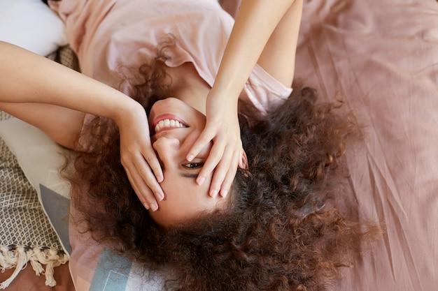 Portret młodej szczęśliwej ciemnoskórej kobiety leżącej na łóżku i twarzy z rękami, ciesząc się słonecznym dniem w domu i uśmiechając się, spędza wolny dzień w domu.