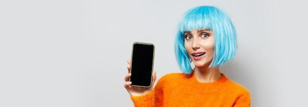 Portret młodej szczęśliwej dziewczyny trzymającej smartfon w dłoni, ubranej w perukę z niebieskimi włosami i pomarańczowy sweter