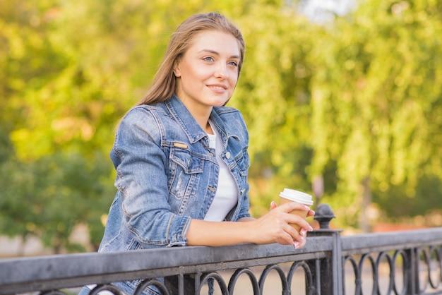Portret młodej, szczęśliwej i ładnej blondynki kobiety z filiżanką kawy w dłoniach