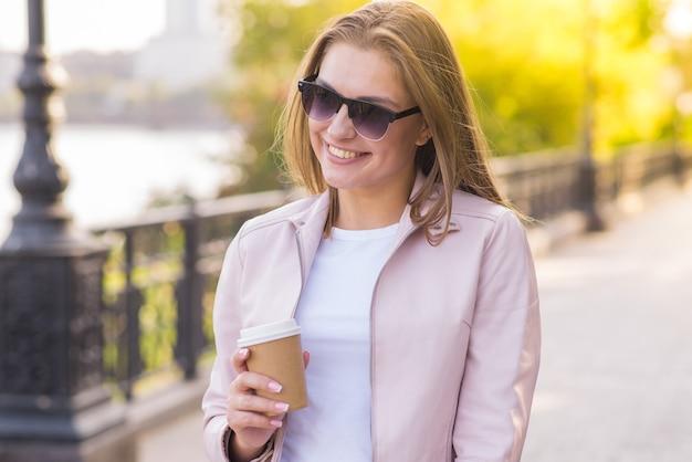Portret młodej, szczęśliwej i ładnej blondynki z filiżanką kawy w dłoniach