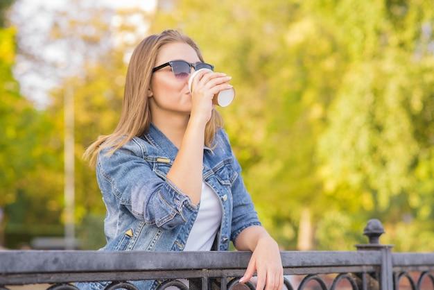 Portret młodej, szczęśliwej i pięknej kobiety blondynka, która pije kawę