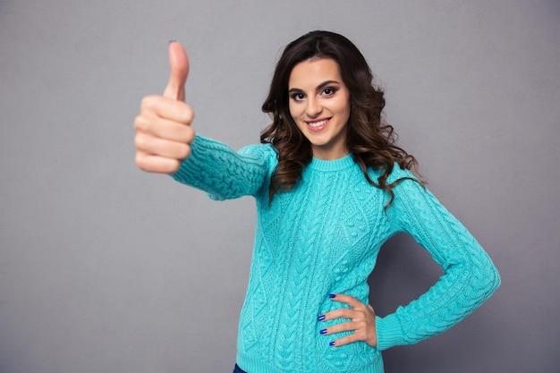 Portret młodej szczęśliwej kobiety pokazujący kciuk nad szarą ścianą