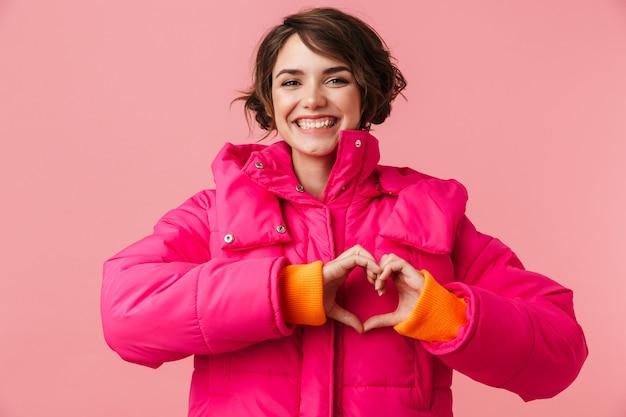 Portret młodej szczęśliwej kobiety w ciepłym płaszczu z wykonywaniem gestu serca i uśmiechem na różowym tle