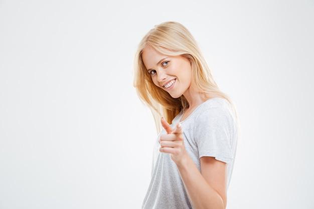 Portret młodej szczęśliwej kobiety wskazującej palcem z przodu