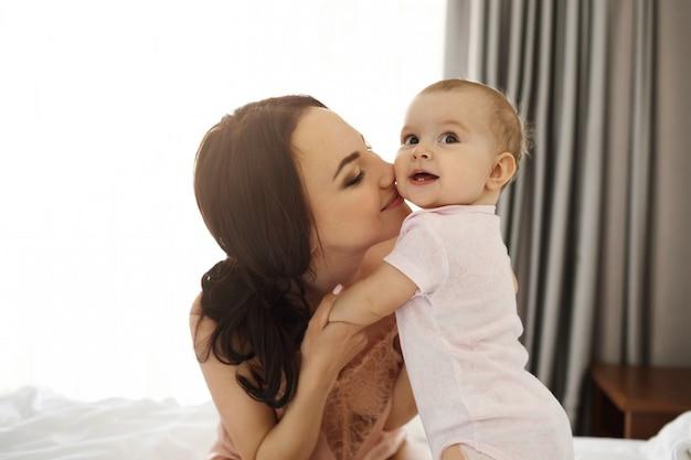 Portret młodej szczęśliwej mamy przetargu i jej córeczki, uśmiechając się, siedząc na łóżku w domu