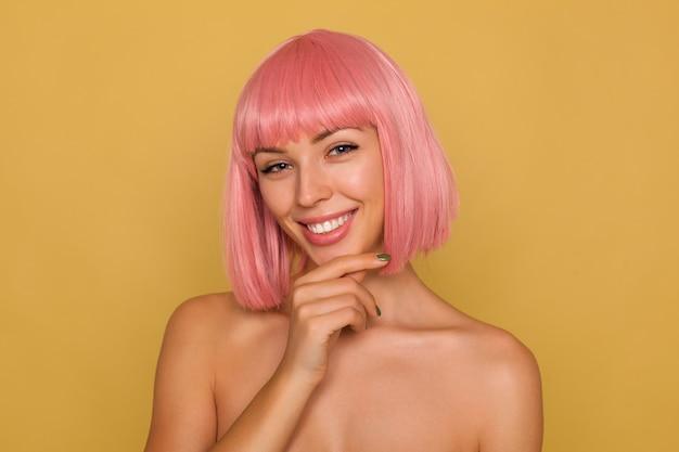 Portret młodej szczęśliwej niebieskookiej różowowłosej kobiety wyglądającej szczęśliwie z uroczym uśmiechem, trzymając uniesioną rękę na brodzie, pozując nad musztardową ścianą