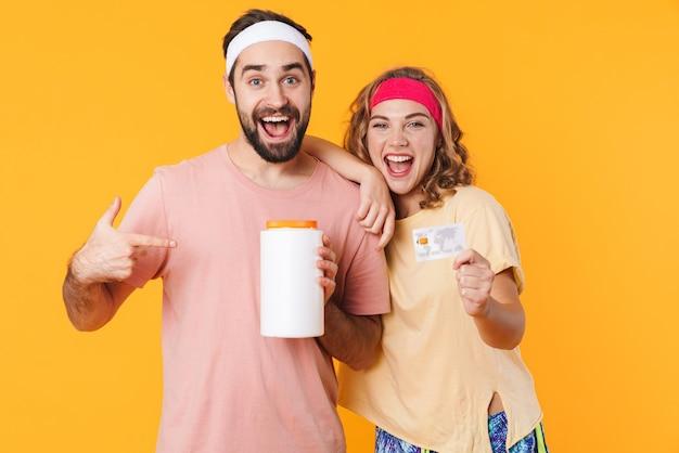 Portret młodej szczęśliwej pary fitness rasy kaukaskiej noszącej opaski na głowę trzymającej słoik białka i kartę kredytową na białym tle
