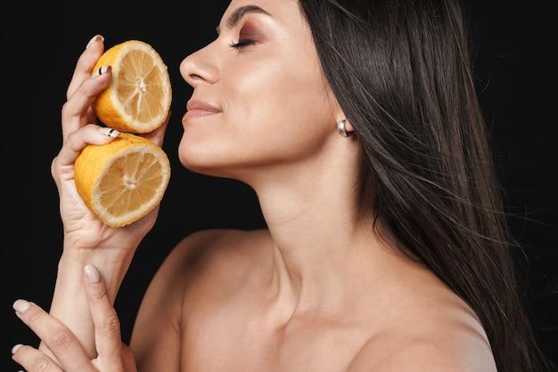Portret młodej szczęśliwej pięknej nagiej kobiety pozuje na białym tle nad czarną ścianą trzymając pomarańczową połowę cytrusów.