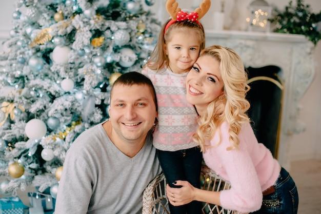 Portret młodej szczęśliwej rodziny w pobliżu choinki