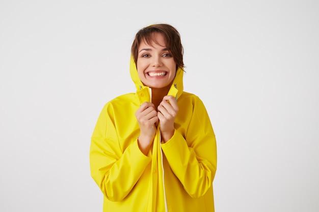 Portret młodej szczęśliwej ślicznej krótkowłosej dziewczyny ubrana w żółty płaszcz przeciwdeszczowy, chowająca się pod kapturem, szeroko się uśmiecha i patrzy w kamerę, stoi nad białą ścianą.