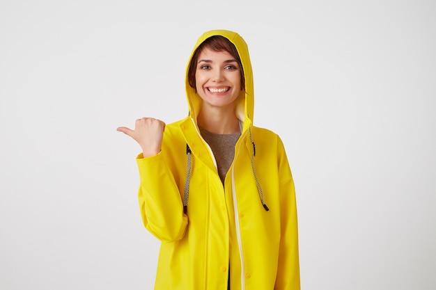 Portret młodej szczęśliwej ślicznej krótkowłosej dziewczyny w żółtym płaszczu przeciwdeszczowym, szeroko się uśmiecha, chce zwrócić na siebie uwagę i wskazuje na skopiowanie miejsca po lewej stronie, stoi nad białą ścianą.