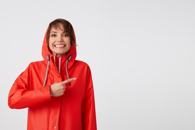 Portret młodej, szczęśliwej, szeroko uśmiechniętej uroczej krótkowłosej kobiety ubranej w czerwony płaszcz przeciwdeszczowy, chce zwrócić twoją uwagę, wskazuje palcem na przestrzeń kopii. na stojąco.