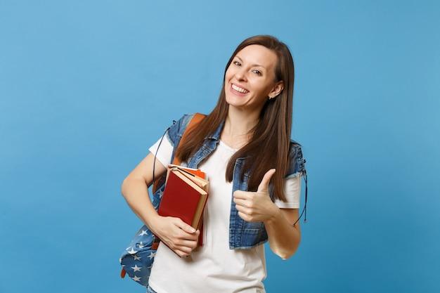 Portret młodej szczęśliwej uroczej studentki z plecakiem pokazując kciuk do góry, trzymając podręczniki szkolne, gotowe do nauki na białym tle na niebieskim tle. edukacja w koncepcji liceum uniwersyteckiego.
