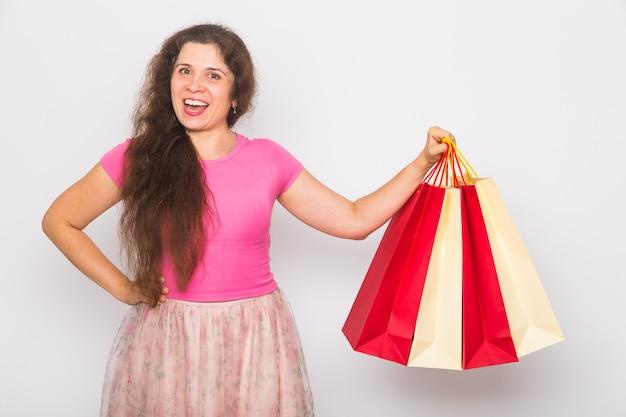 Portret młodej szczęśliwej uśmiechniętej kobiety z torba na zakupy, nad białym tłem. koncepcja zakupu, sprzedaży i ludzi.