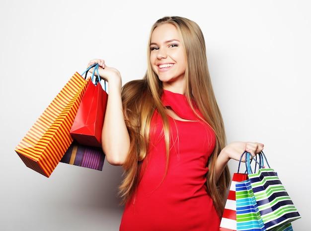 Portret młodej szczęśliwej uśmiechniętej kobiety z torbami na zakupy, na białym tle