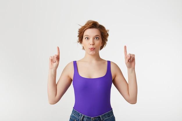"""Portret młodej, szczęśliwej, zdumionej, atrakcyjnej krótkowłosej dziewczyny, ubrana w fioletową koszulkę, patrząc, mówi ustami """"wow"""", a palce wskazujące skierowane są w górę na przestrzeń kopii odizolowaną na białej ścianie."""