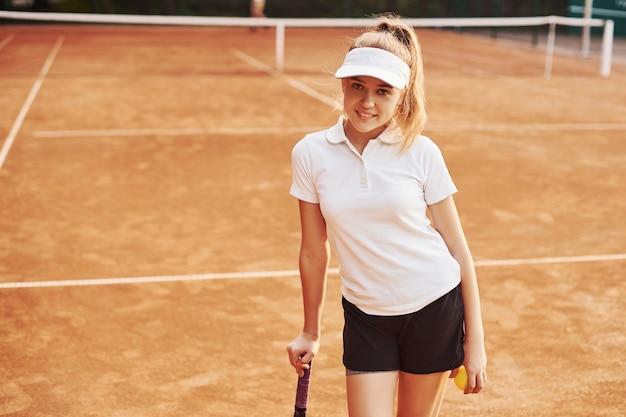 Portret młodej tenisistki w sportowej odzieży jest na boisku na zewnątrz.