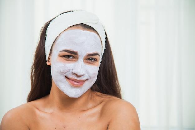 Portret młodej twarzy świeżej kobiecej twarzy w masce z białej glinki twarzy. domowa pielęgnacja urody. koncepcja pielęgnacji skóry i odmładzania.