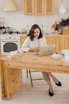 Portret młodej udanej kaukaskiej freelancerki siedzącej przy biurku w domu pewna siebie kobieta pracuje online na laptopie w domu