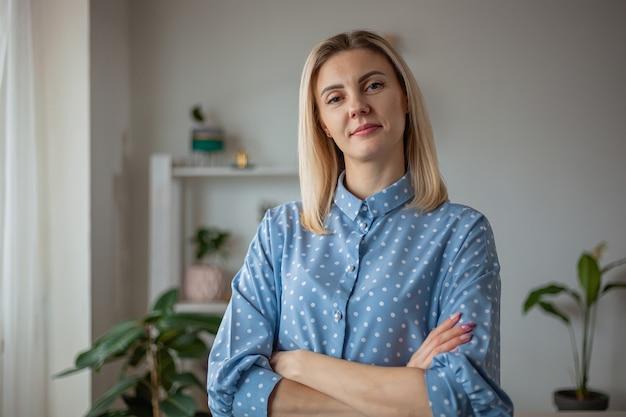 Portret młodej ufnej kobiety stojącej w domu