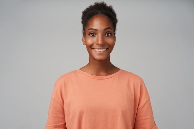 Portret młodej uroczej ciemnoskórej kręconej kobiety z fryzurą kok, wyglądającą pozytywnie z uroczym uśmiechem, odizolowaną na szaro w codziennym noszeniu