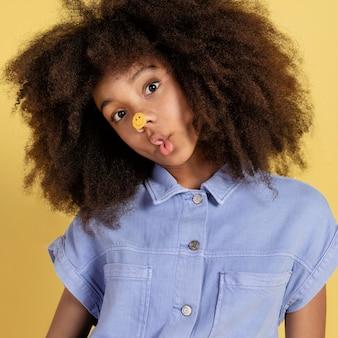 Portret młodej uroczej dziewczyny pozuje z naklejkami emoji na twarzy