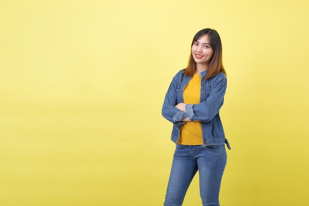 Portret młodej, uroczej i wysportowanej tajskiej dziewczyny z azji w studio na zwykłym żółtym tle