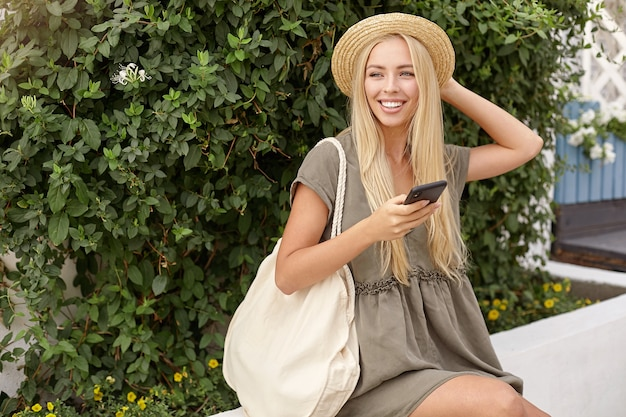 Portret młodej uroczej kobiety z długimi blond włosami, trzymającej kapelusz staw, ubrana w lnianą sukienkę na co dzień, pozująca na zielonym podwórku w jasny dzień