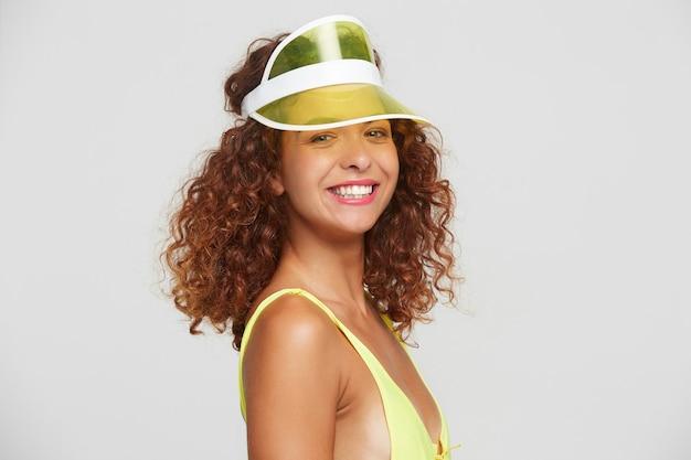 Portret młodej uroczej rudowłosej kręconej kobiety z naturalnym makijażem pokazując jej białe idealne zęby, uśmiechając się radośnie do kamery, pozując na białym tle