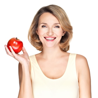 Portret młodej uśmiechnięta zdrowa kobieta z czerwonym jabłkiem na białym tle.
