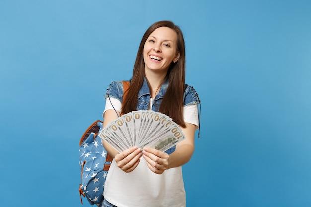 Portret młodej uśmiechniętej atrakcyjnej kobiety studentki w dżinsowych ubraniach z plecakiem trzymającym pakiet wiele dolarów, pieniądze w gotówce na białym tle na niebieskim tle. edukacja w liceum ogólnokształcącym.