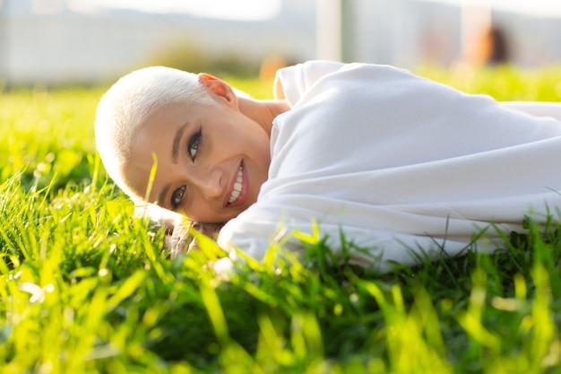 Portret młodej uśmiechniętej europejskiej krótkowłosej kobiety leżącej na zielonej trawie łące lato park piękna...