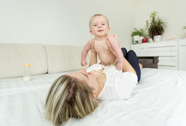 Portret młodej uśmiechniętej kobiety bawiącej się z dzieckiem na łóżku