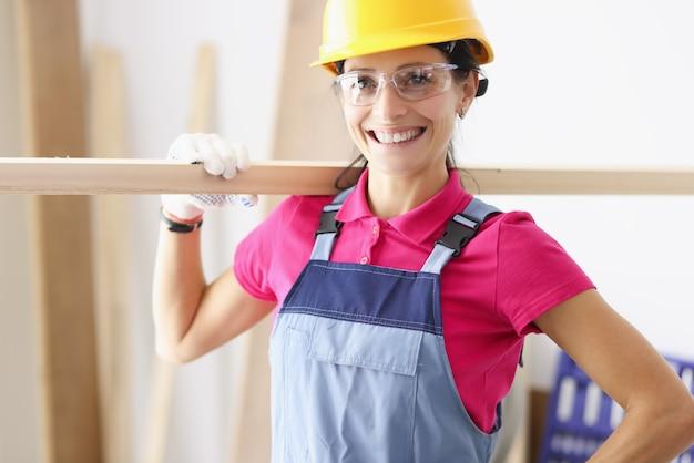 Portret młodej uśmiechniętej kobiety stolarza budowniczego