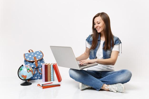 Portret młodej uśmiechniętej kobiety studenta trzymającej za pomocą laptopa komputerowego siedzącego w pobliżu kuli ziemskiej, plecaka, podręczników szkolnych na białym tle