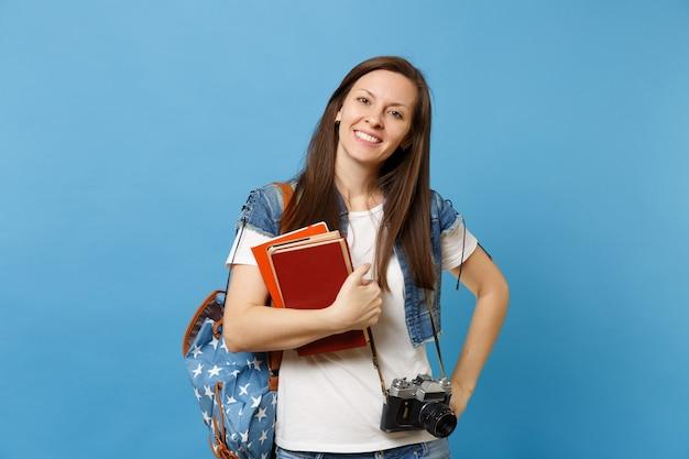 Portret młodej uśmiechniętej kobiety studentki z plecakiem i retro vintage aparat fotograficzny na szyi, trzymając podręczniki szkolne na białym tle na niebieskim tle. edukacja w koncepcji liceum uniwersyteckiego.