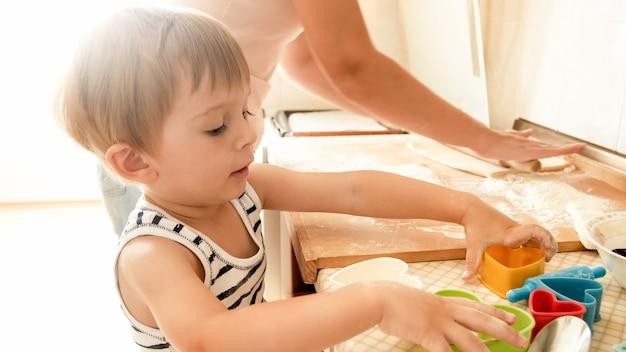 Portret młodej uśmiechniętej matki uczy swojego 3-letniego chłopca pieczenia i robienia ciasteczek w kuchni