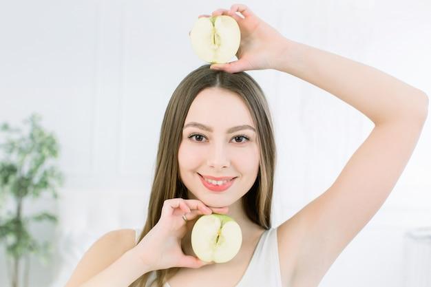 Portret młodej uśmiechniętej pięknej dziewczyny z dwiema połówkami jabłek w dłoniach, powyżej i poniżej twarzy. ładna kaukaska dziewczyna trzyma halfs jabłko i pozuje na lekkim tle