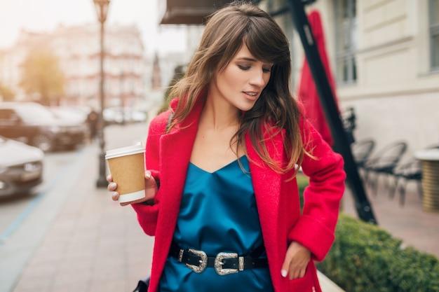 Portret młodej uśmiechniętej pięknej stylowej kobiety spaceru na ulicy w czerwonym płaszczu, picia kawy